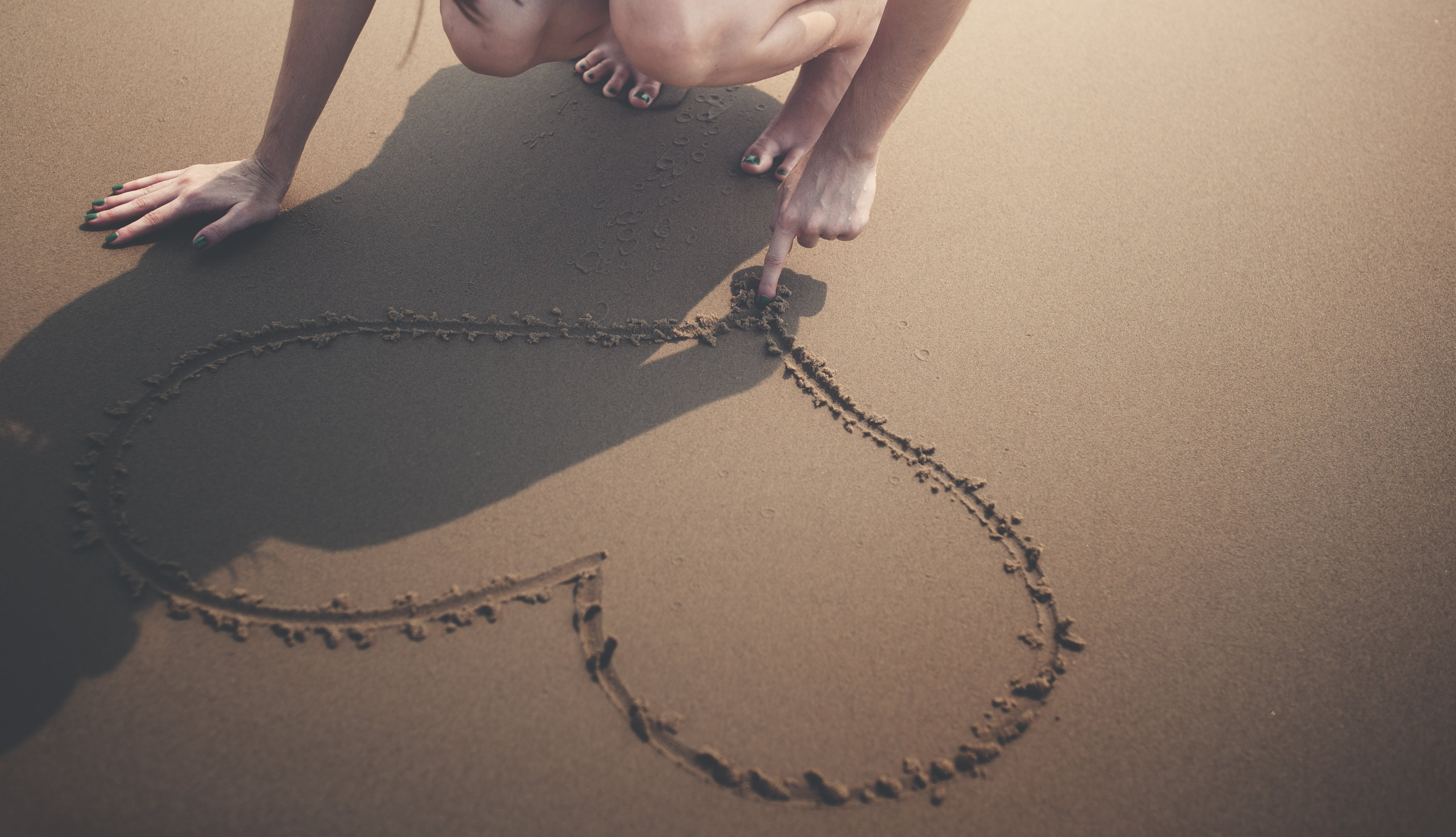 Woman Draws Heart on Sand
