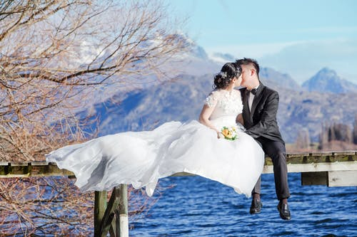 Man and Woman Kissing on Top of Water Dock