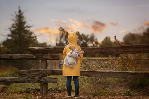Standing Person Carrying Gray Moose Plush Toy