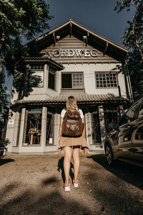 Woman Carrying Brown Leather Backpack Standing In Front Of A Building