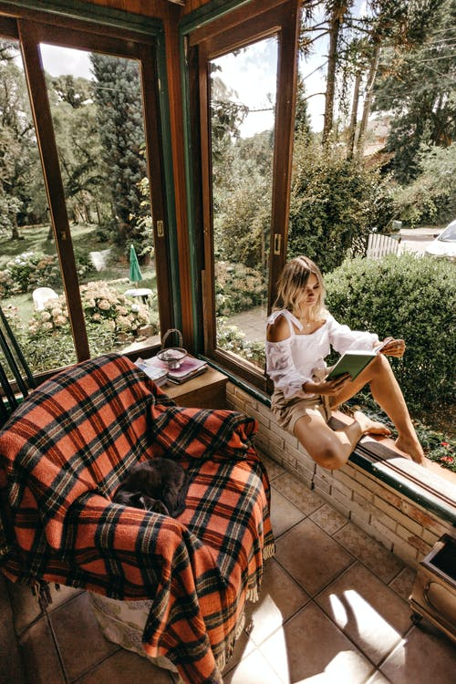 Woman Sitting On Window Sill While Reading A Book