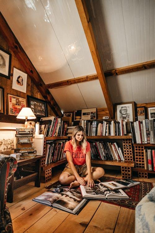 Photo Of Woman Sitting Near Bookshelves