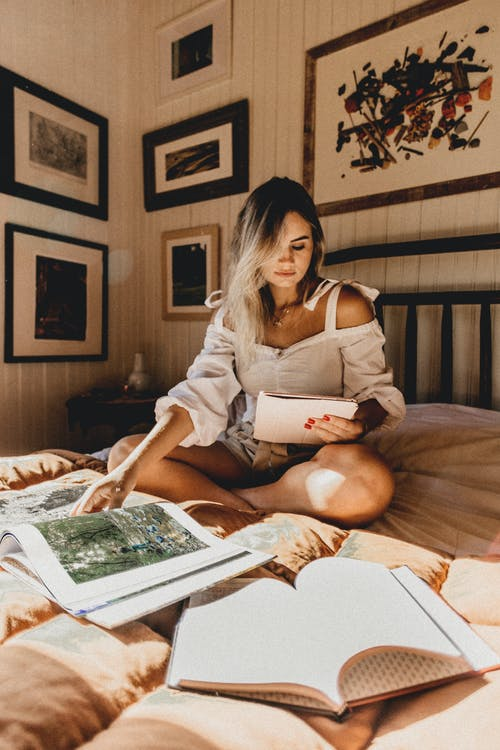Photo Of Woman Reading Book On Bed