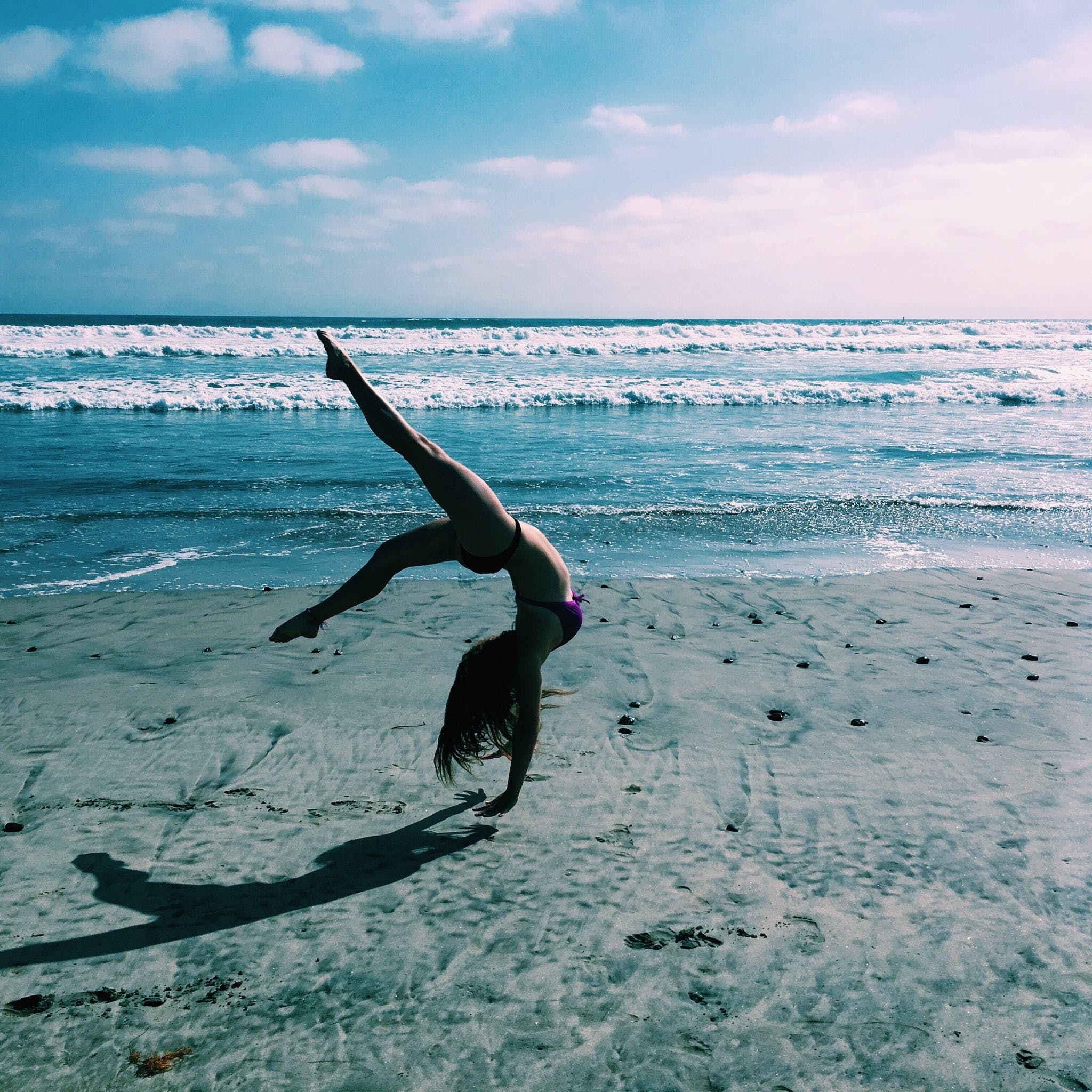 Woman Doing Handstand on Sand Beach