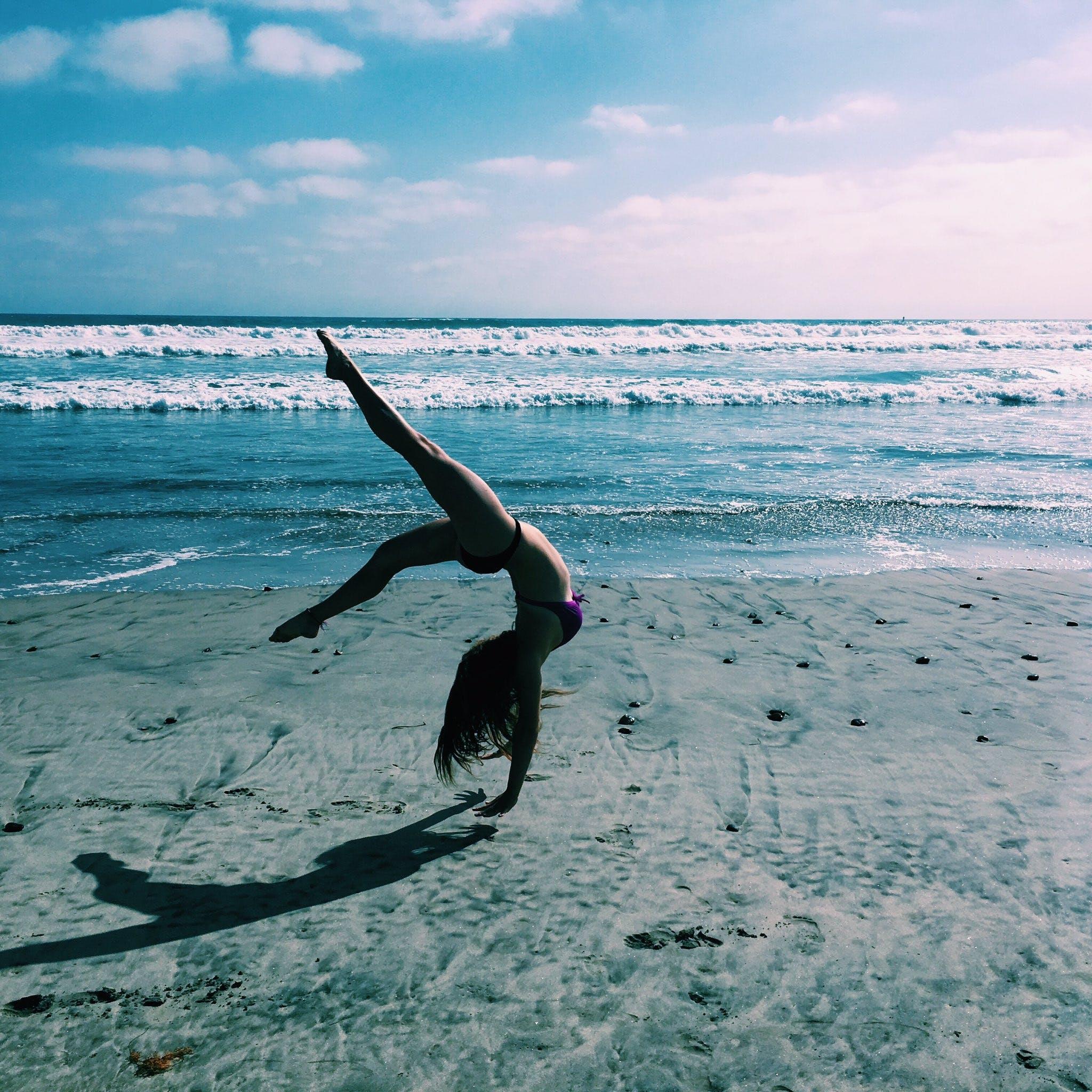 Woman Doing Handstand on Sand Beach