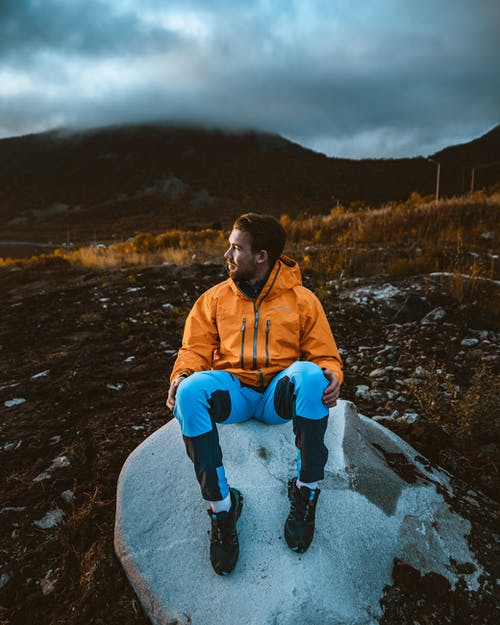 Photo Of Man Sitting On Rock