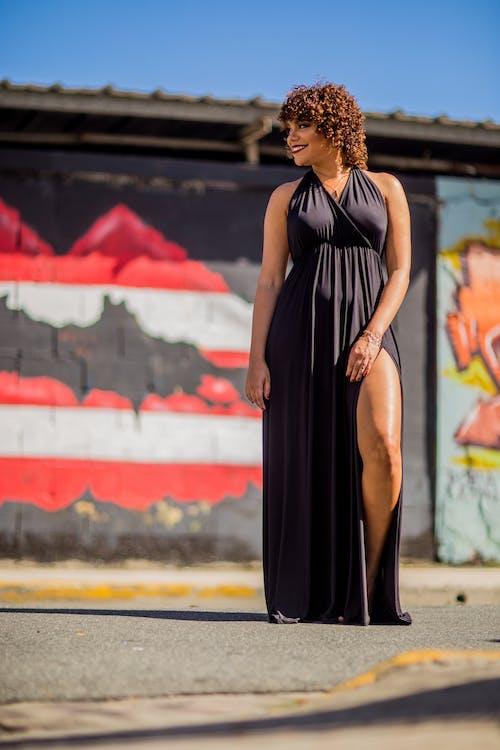 Low Angle Photo Of A Woman Wearing Black Halterneck Side-slit Dress