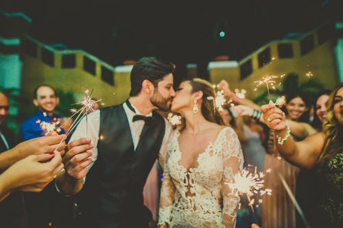 Photo of Couple Kissing Near People Holding Sparklers