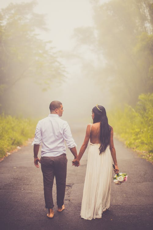 Photo of Couple Holding Hands While Walking Barefoot