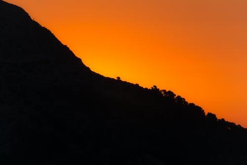 akşam Güneşi, dağ, deniz kenarı, gölgeler içeren Ücretsiz stok fotoğraf