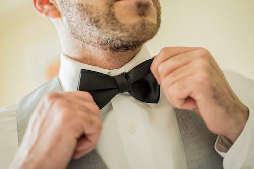 Pria Memegang Dasi Kupu Kupu