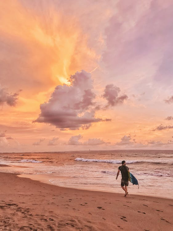 Man Walking On Shore While Holding Surfboard