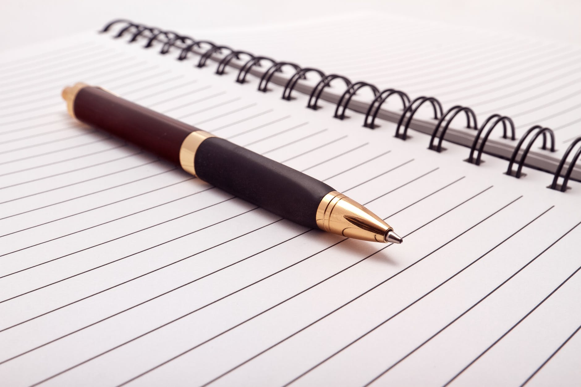 Black Fountain Pen Placed on Spiral Notebook