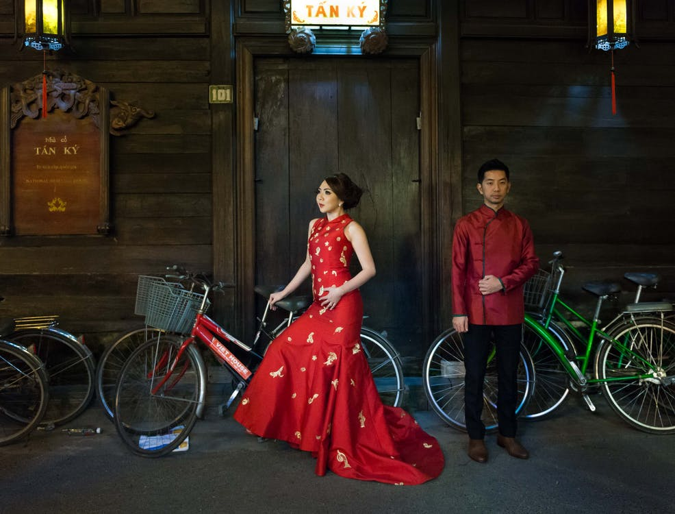 Man And Woman in Red Attire Beside Bikes