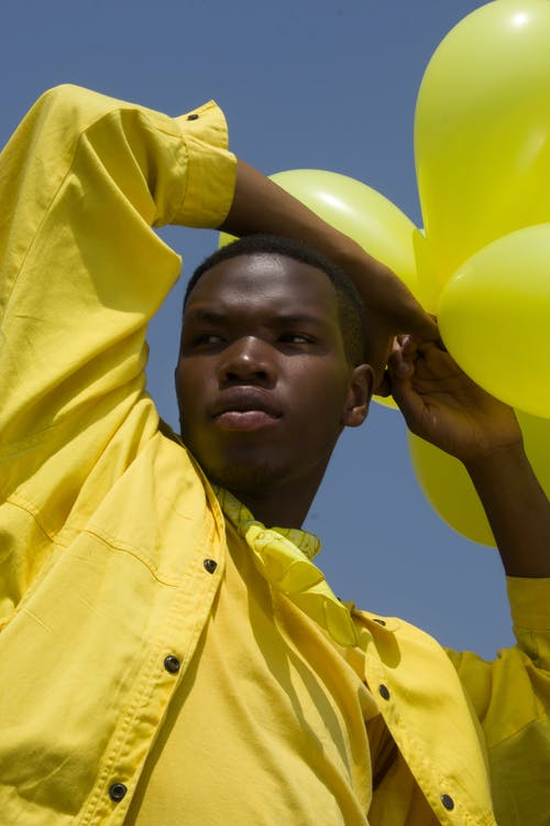 Man Holding Yellow Balloons