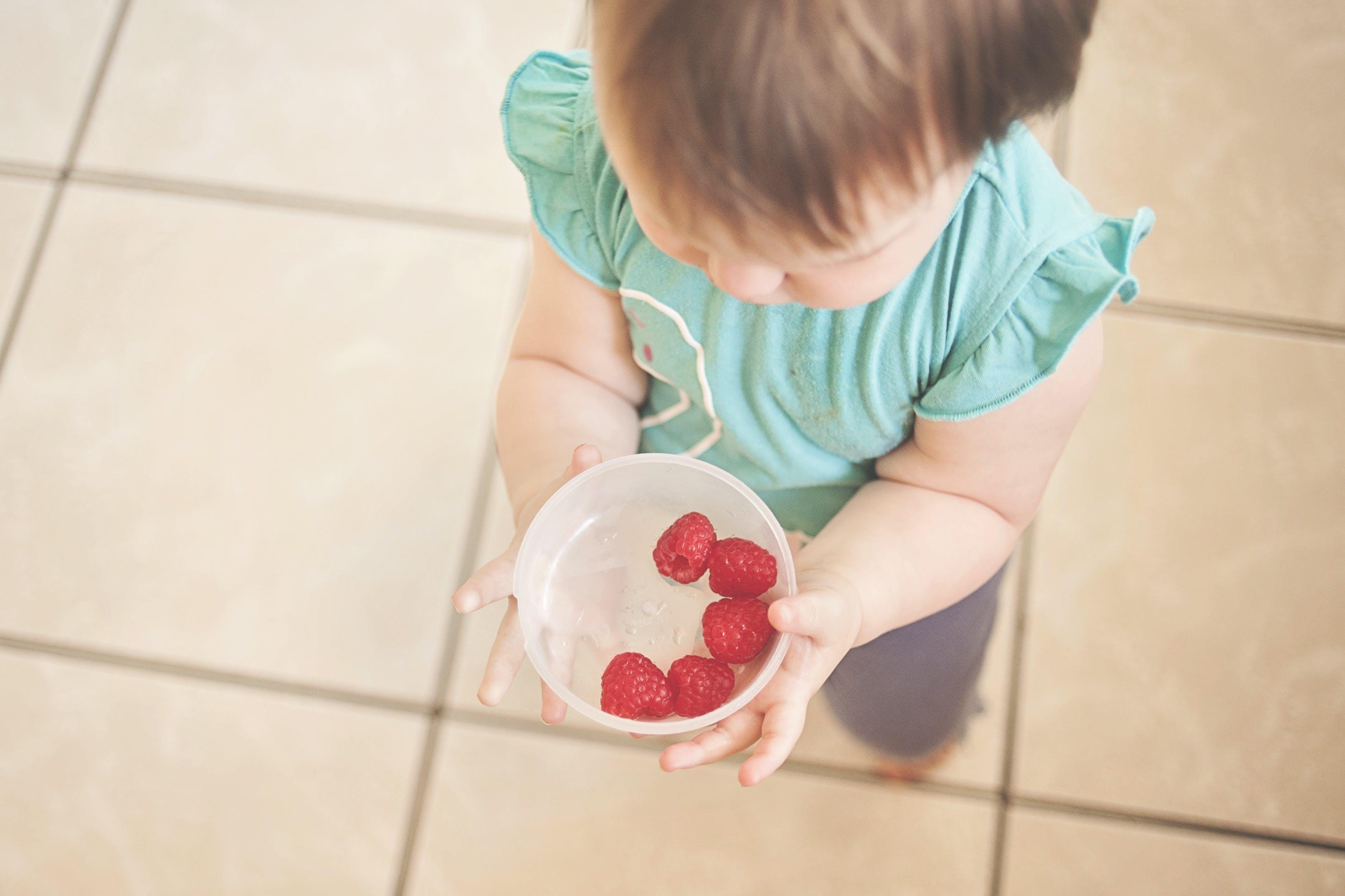 Toddler Holding White Bowl