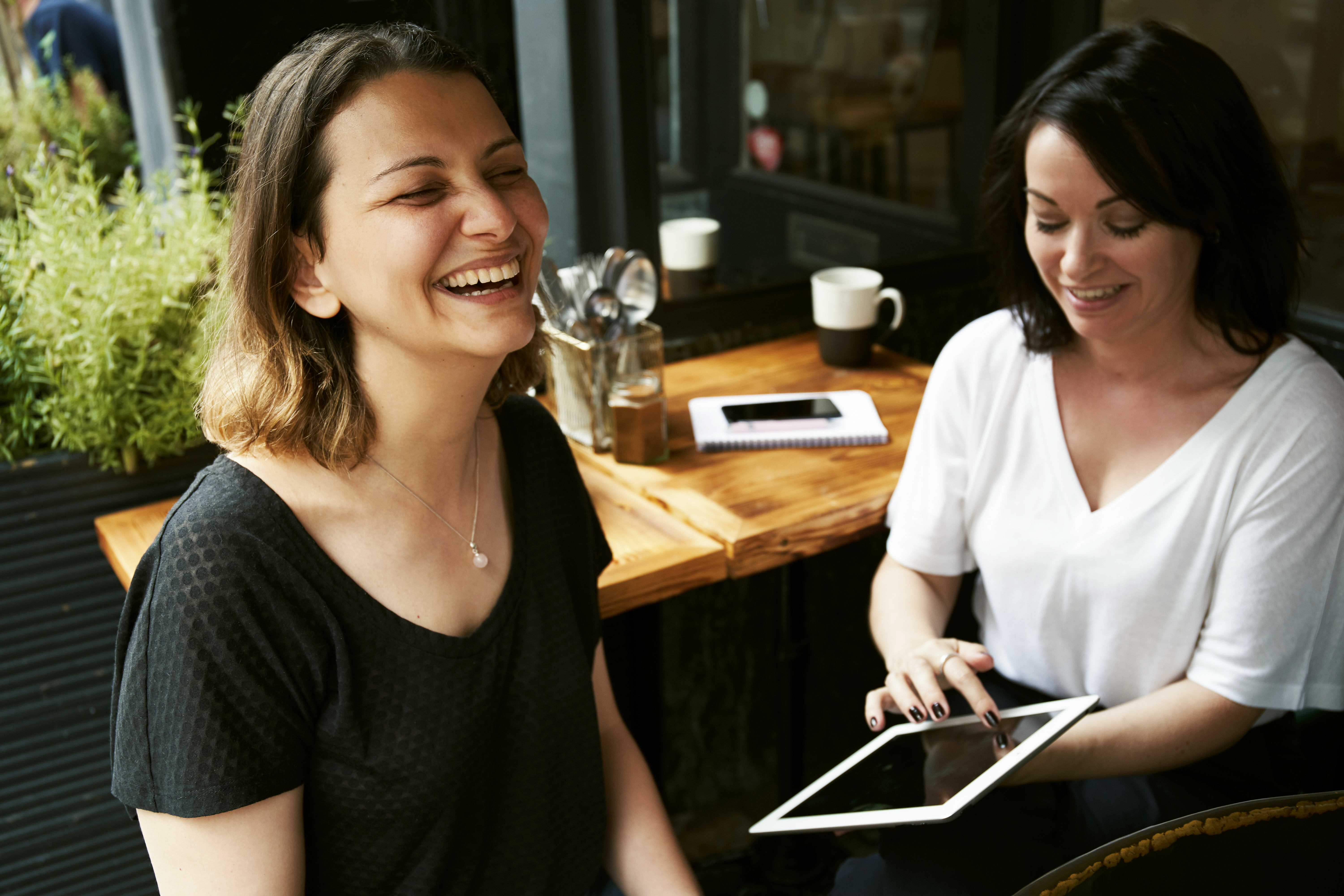 Photo of Two Women Sitting While Laughing
