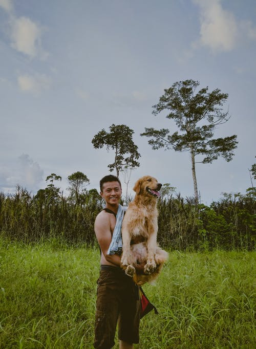 Photo Of Man Carrying Dog
