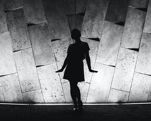Monochrome Photo of Person Standing Near Wall