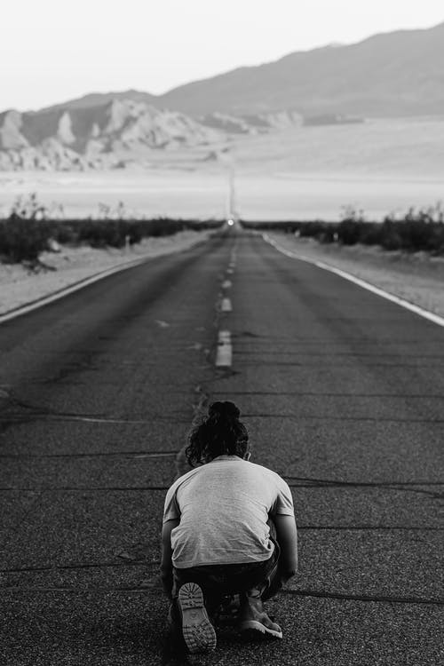 Person Kneeling on Highway