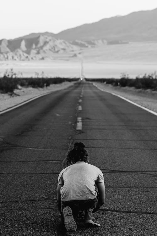 Person Kneeling on Highway
