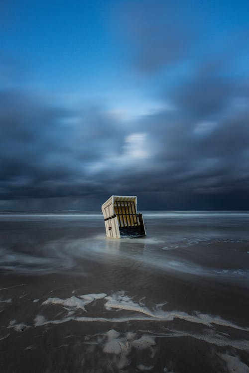Brown Wooden Lifeguard House on Beach Shore Under Cloudy Sky