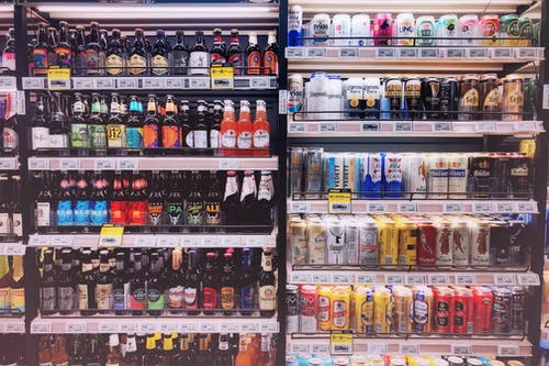 Assorted Bottles and Cans in Commercial Coolers