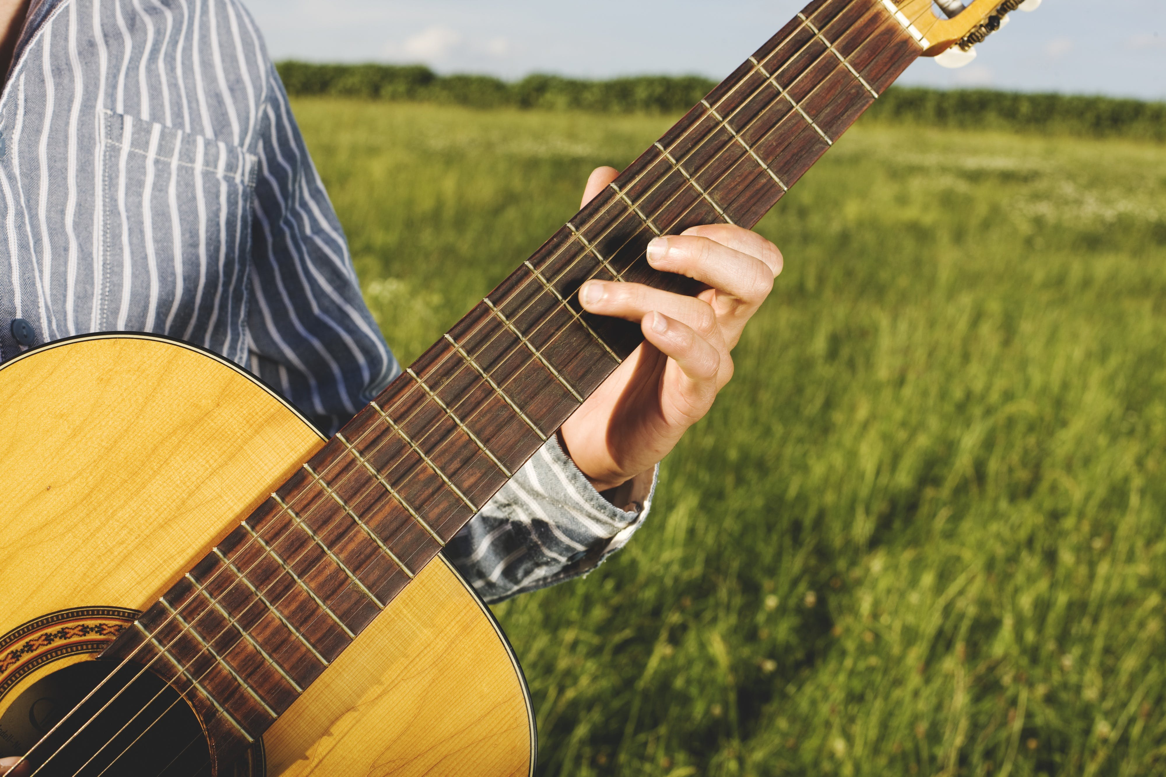 Person Playing Guitar in Grass Field