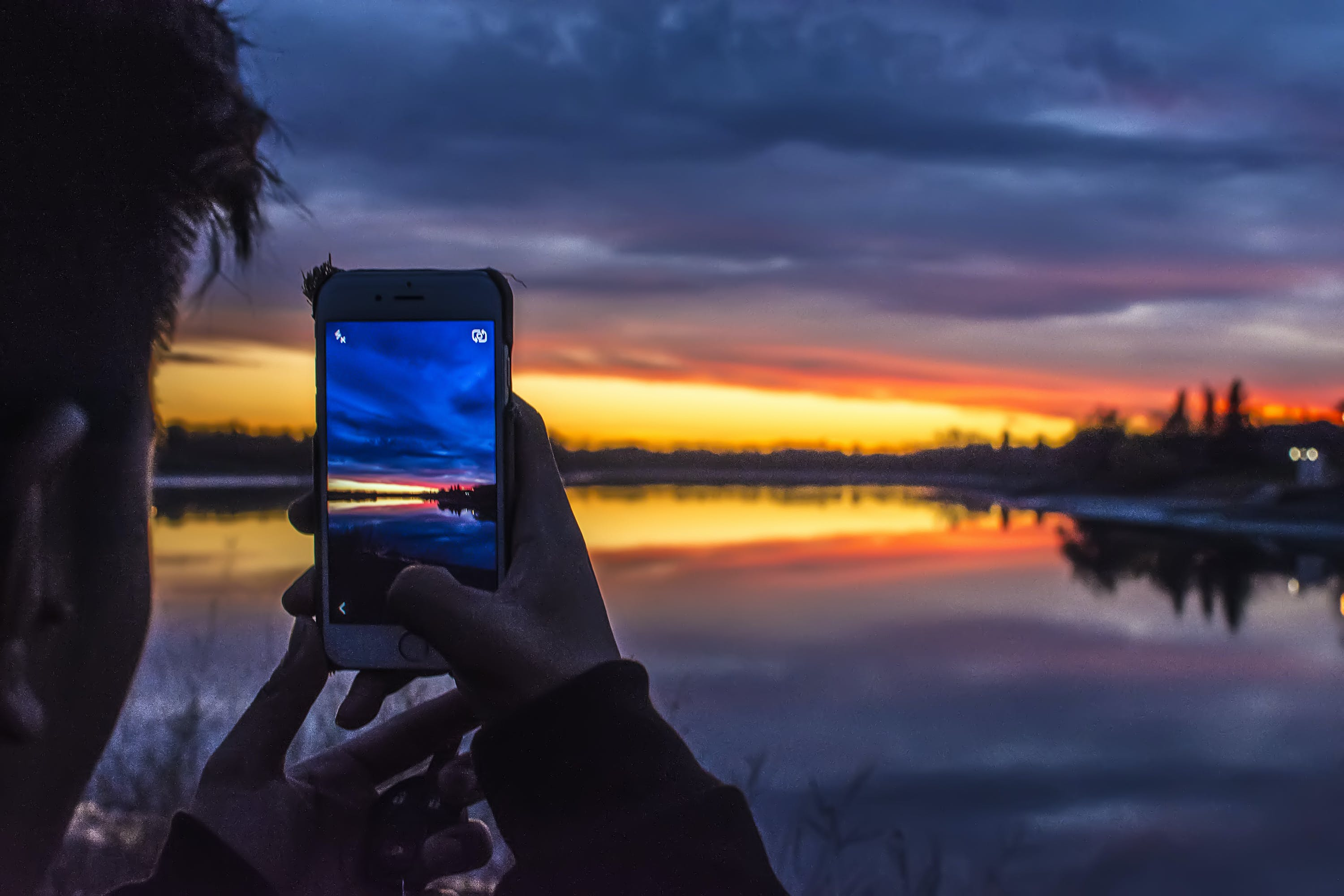 Person Holding Smartphone Taking Photo of Lake Under Golden Hour