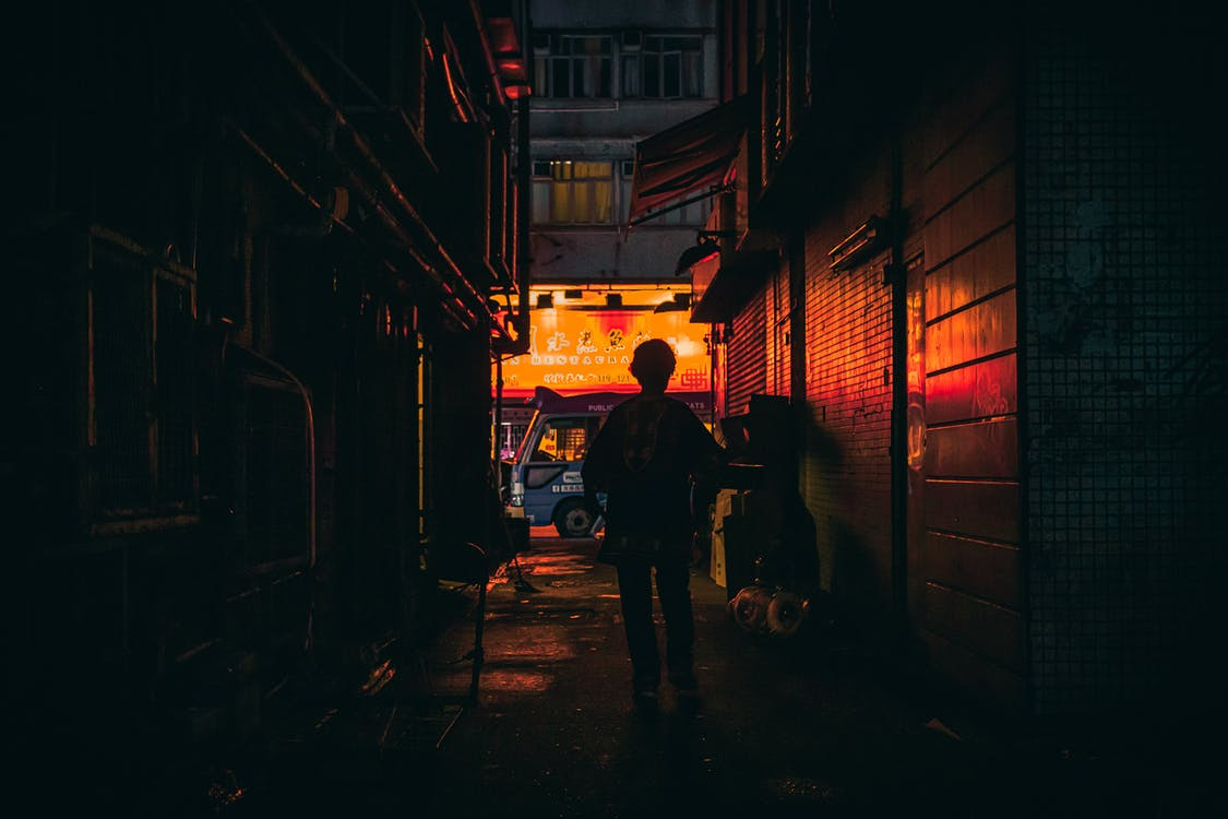 Silhouette Photo of Person Walking in Alley