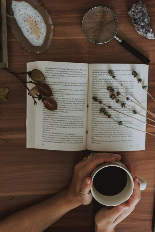 Hands Holding a Cup of Coffee and an open book  in front