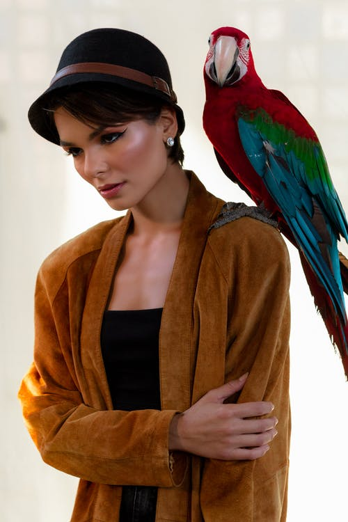 Young serious female with glowing makeup standing with exotic bird on shoulder and looking down