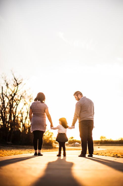 Photo of Family Standing Outdoors During Golden Hour
