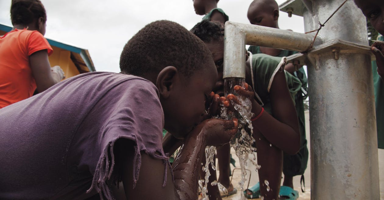 Close-up Of Two Children Drinking Water on Water Pump
