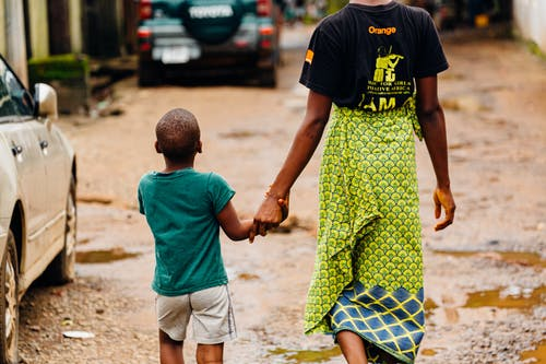 Man and Boy Walking on Beside Vehicle
