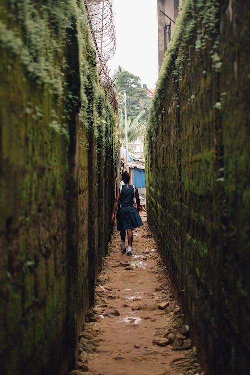 女人走在混凝土墙之间的小巷