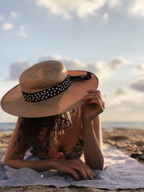 Woman Wearing Bikini Top And Brown Hat Sunbathing On The Beach