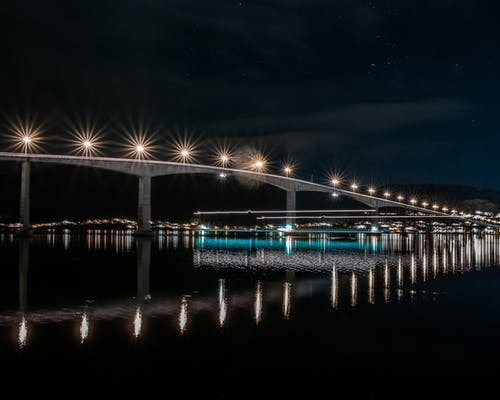 Blue Lighted Bridge over Water during Night Time