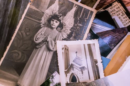 Close-up Of Old Black and White Photos Of A Young Girl In An Angel Costume And A Church