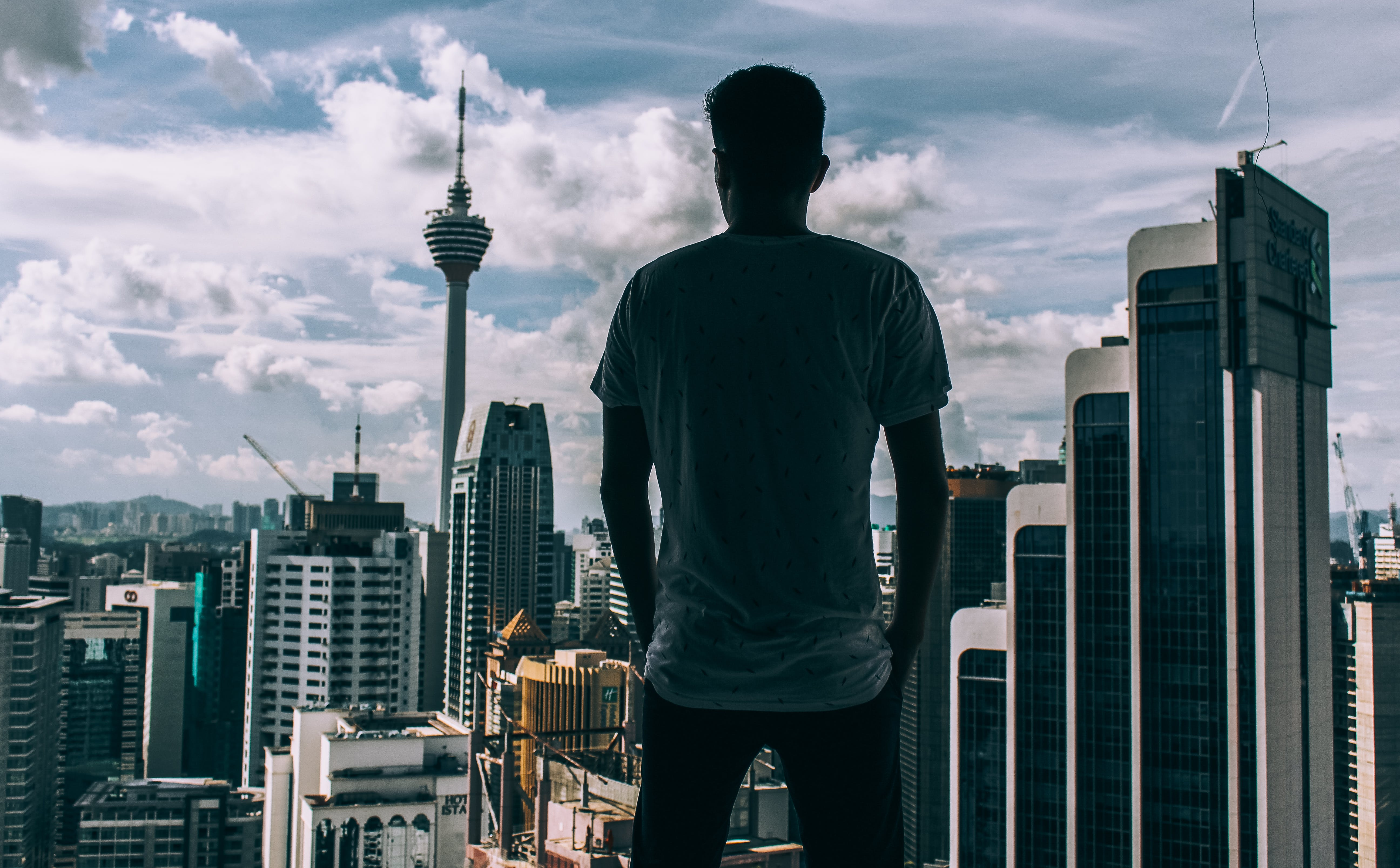 Man Standing While Facing Concrete Buildings