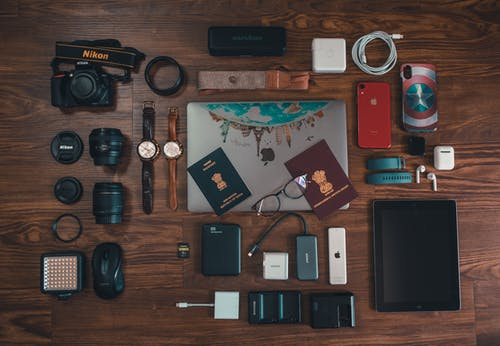 Passports, Camera, Battery Charger, Watches, and Cables on Brown Wooden Surface