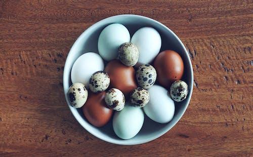 ahşap masa üstü, beyaz yumurtalar, bıldırcın yumurtası, çanak içeren Ücretsiz stok fotoğraf