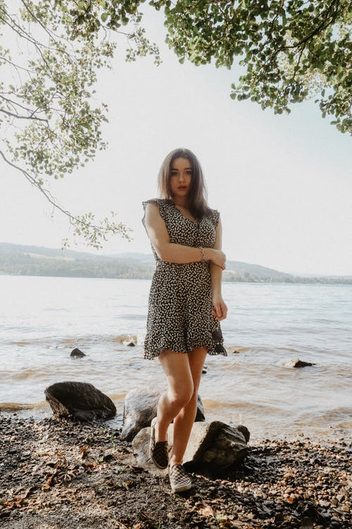 Woman in Black and White Polka Dot Dress Standing on Rock Near Sea