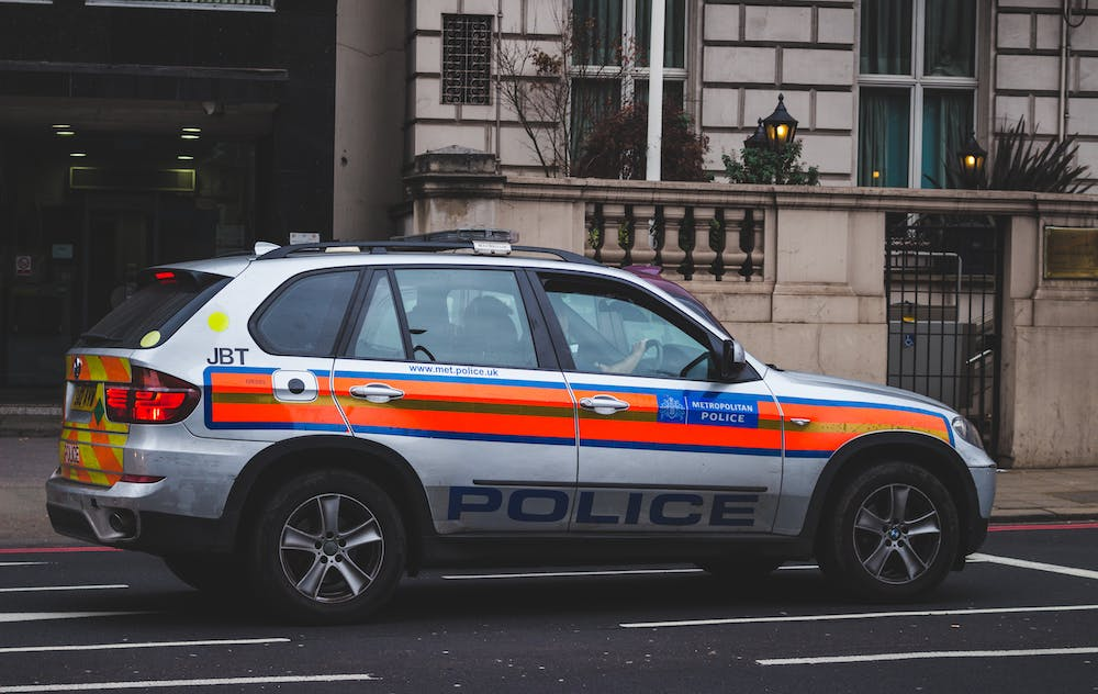 Police car passing by a road.   Photo: Pexels