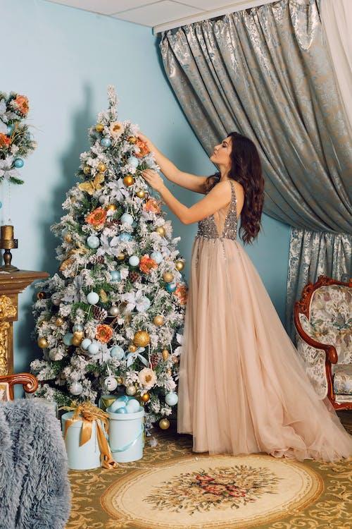 Woman Arranging White Christmas Tree