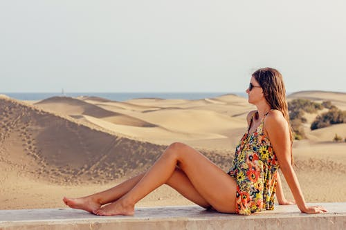 Woman Sitting on Sand at Beach Against Sky