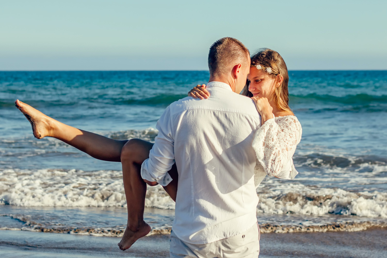 Man Carrying Woman Beside Shoreline