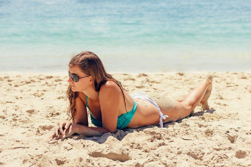 Woman Wearing Blue Bikini Top on Sand