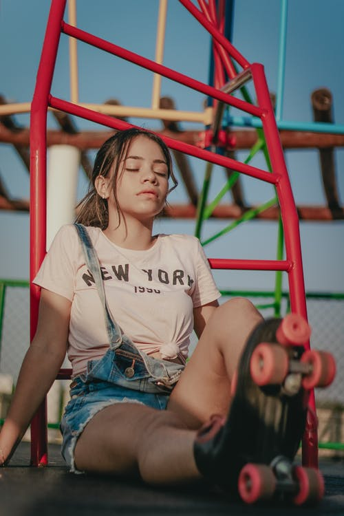 Photo of Woman in Pink T-shirt, Blue Dungarees, and Roller Skates Sitting on the Floor with her Eyes Closed With Jungle Gym in the Background