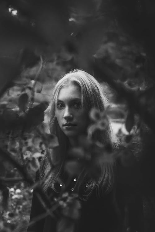 Greyscale Photo of Woman Near Bush